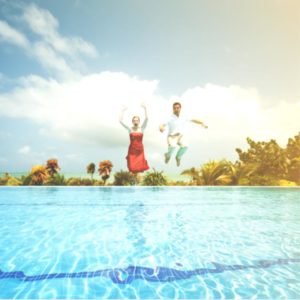 Young couple jumping in a pool